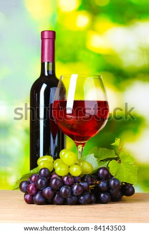 Ripe grapes, bottle and  glass of wine on  green background - stock photo