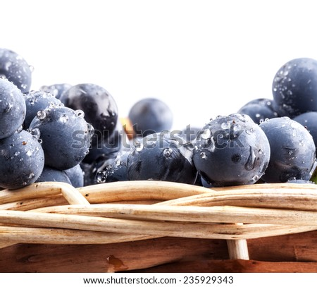 Ripe grapes in wicker basket, closeup, on white background - stock photo