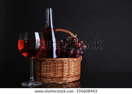 Ripe grapes, wine glass and bottle of wine on black background - stock photo