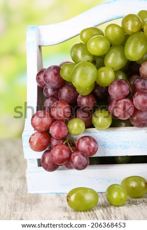 Ripe green and purple grapes in basket on wooden table on natural background - stock photo