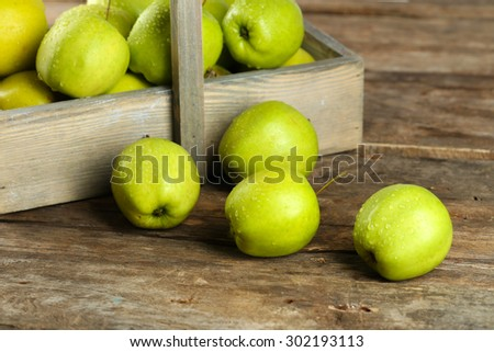 Ripe green apple in crate on wooden table close up - stock photo