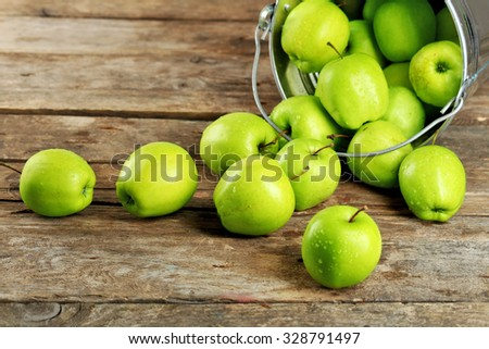 Ripe green apple in metal bucket on wooden table close up - stock photo