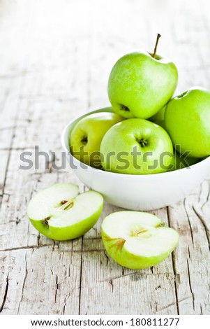 ripe green apples in bowl closeup on rustic wooden background - stock photo
