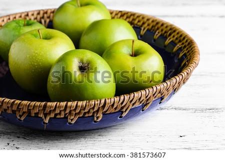 Ripe green apples in charming handmade basket - stock photo