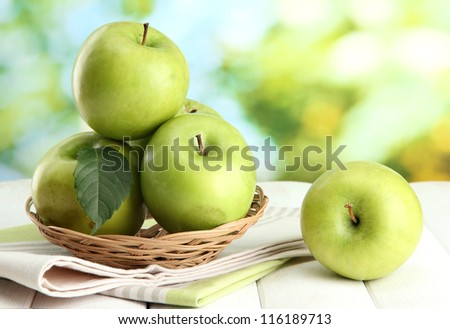 Ripe green apples with leaves in basket, on wooden table, on green background - stock photo