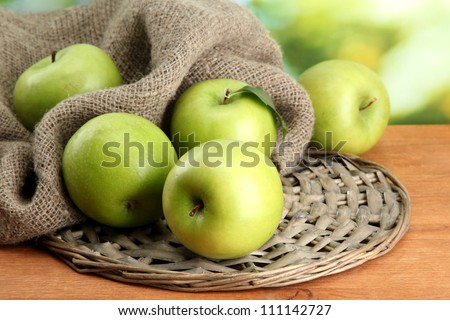 Ripe green apples with leaves on burlap, on wooden table, on green background - stock photo