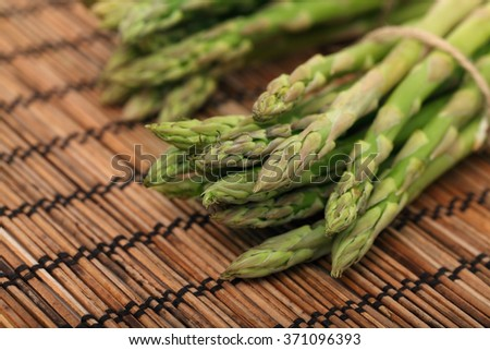 Ripe green mini asparagus on wooden mat background - stock photo