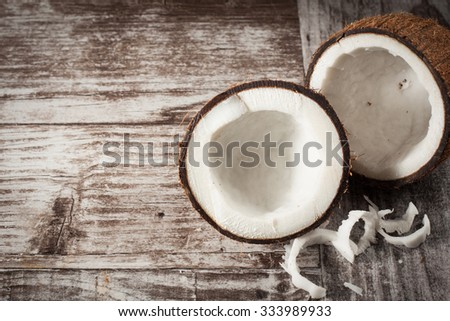 Ripe half cut coconut on a wooden backgroundRipe half cut coconut on a wooden background - stock photo