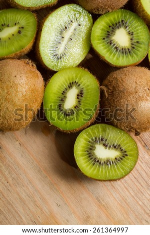 Ripe half kiwi fruits against a rustic wooden background. - stock photo