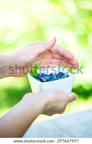 Ripe Honeysuckle Berries in Bowl on Hands, Macro Shot, Shallow DOF, Selective Focus - stock photo