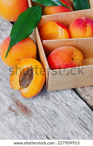 ripe juicy apricots in a cardboard box on a wooden background. health and diet food. copy space for text - stock photo