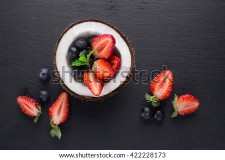Ripe juicy berries - strawberries, blueberries and blackberries in a fresh coconut on black stone background, top view. Healthy food. Summer time - stock photo