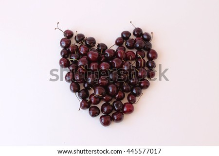 ripe juicy cherries are laid out in the shape of a heart on a light background - stock photo