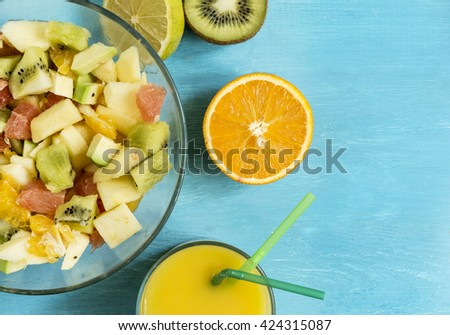 ripe juicy citrus fruit fruit salad juice ice on a blue wooden table top view - stock photo