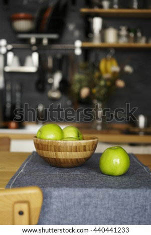 Ripe juicy green apples in a bowl on the kitchen table in the loft-style and rustic. - stock photo