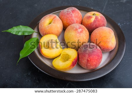 Ripe juicy peaches on a plate ready to eat - stock photo