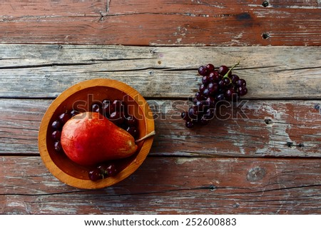 Ripe juicy pear in bowl on rustic wood. Pear autumn harvest. Fruit background. Top view. Copy space. - stock photo