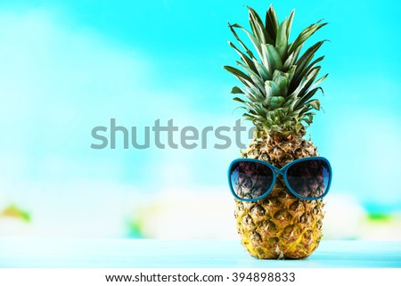 Ripe juicy pineapple in sun glasses on blue blurred background - stock photo