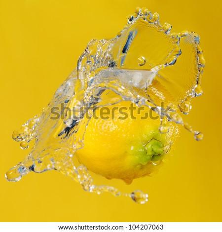 Ripe Lemon in water splash on yellow background - stock photo