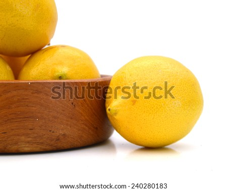 ripe lemons in wooden bowl on a white background  - stock photo