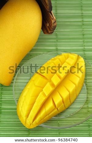 Ripe mango on a plate and put the mango wood. - stock photo