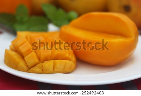 Ripe mangoes with mint leaves on a plate - stock photo