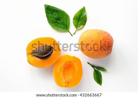 Ripe orange apricots with leaves on white background. Isolated fruit.  - stock photo