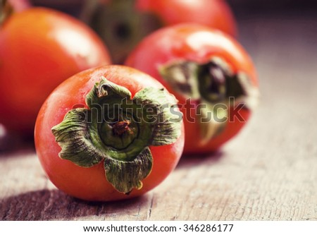 Ripe orange persimmons on an old wooden table in rustic style, selective soft focus - stock photo