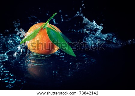 Ripe orange with leaves on a black background with water splashes - stock photo