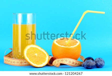 Ripe oranges and juice as symbol of diet on blue background - stock photo