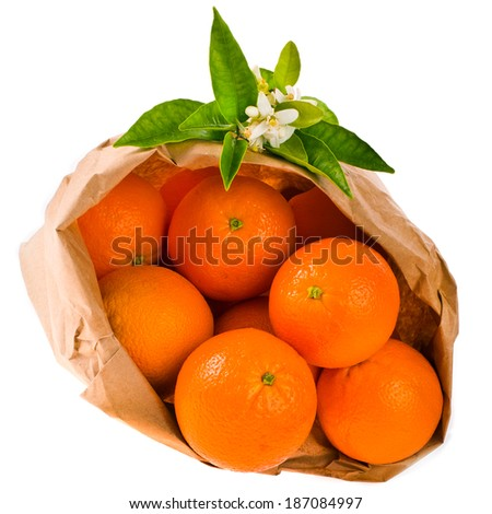 ripe oranges lie in a paper bag  decorated with leaves and flowers of orange  isolated on white background - stock photo