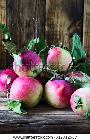 Ripe organic apples on wooden background, harvest time concept - stock photo