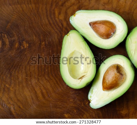 ripe organic avocado cut in half on a wooden background - stock photo