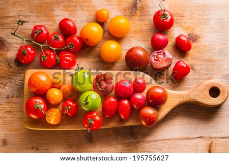 Ripe, organically grown tomatoes in a variety of colours: yellow, orange, green, brown and red. - stock photo