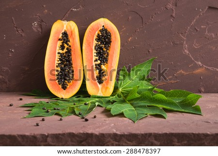 Ripe papaya with green leaf on brown stone table over stone grunge background. - stock photo