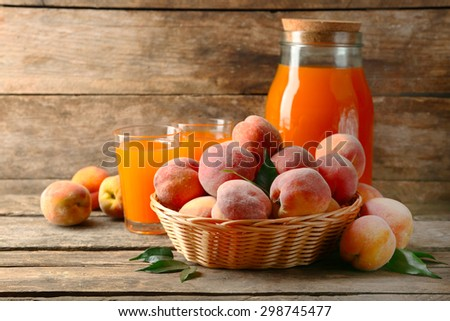 Ripe peaches and juice on wooden background - stock photo