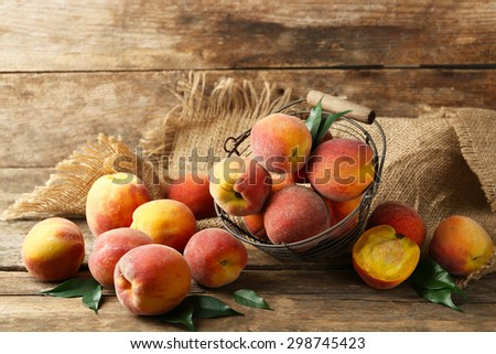 Ripe peaches in basket on wooden background - stock photo