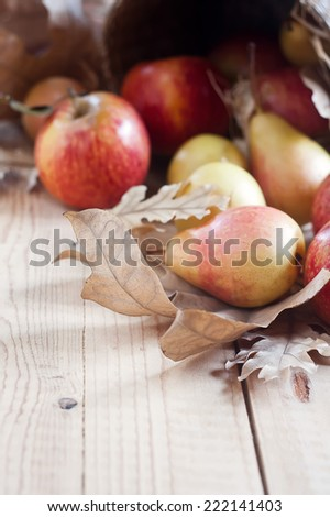 Ripe pears and apples with dry fall leaves on wooden background. Selective focus. Copyspace background. - stock photo