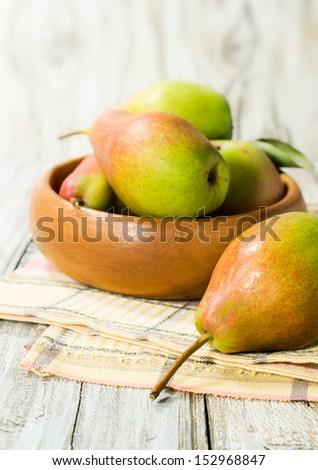 Ripe pears in a wooden bowl close-up - stock photo