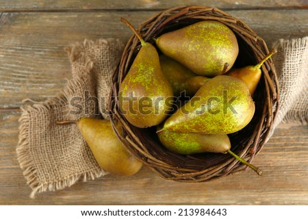 Ripe pears in wicker basket, on wooden background - stock photo