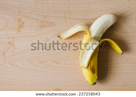 ripe peel banana on wooden cutting board top view - stock photo