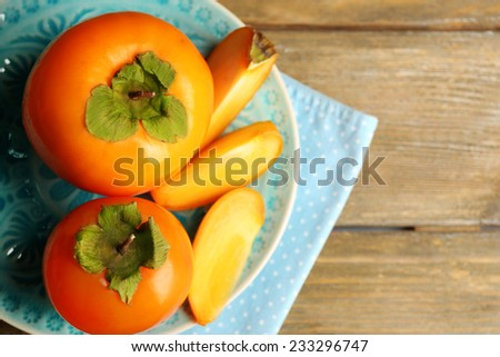 Ripe persimmons on plate, on wooden background - stock photo