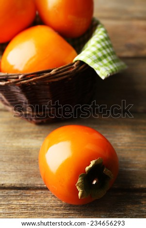 Ripe persimmons on wooden background - stock photo