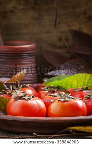 Ripe persimmons with leaves on a clay plate in a rustic style, selective focus - stock photo