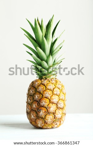 Ripe pineapple on a white wooden table - stock photo