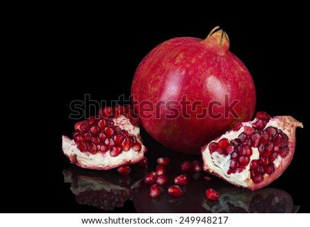 Ripe pomegranate fruit isolated on a black background - stock photo