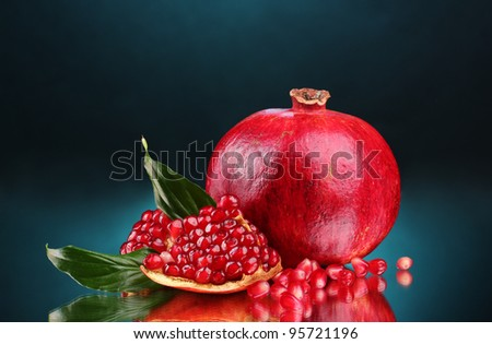 ripe pomegranate fruit with leaves on blue background - stock photo