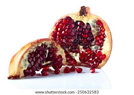 ripe pomegranate isolated on a white reflexive background - stock photo