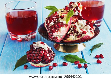 ripe pomegranate seeds and fresh pomegranate juice on a blue wooden background.health and diet food - stock photo