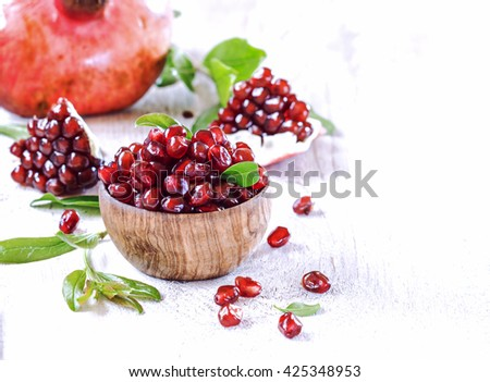Ripe pomegranate seeds in a wooden bowl on a white  vintage background. - stock photo